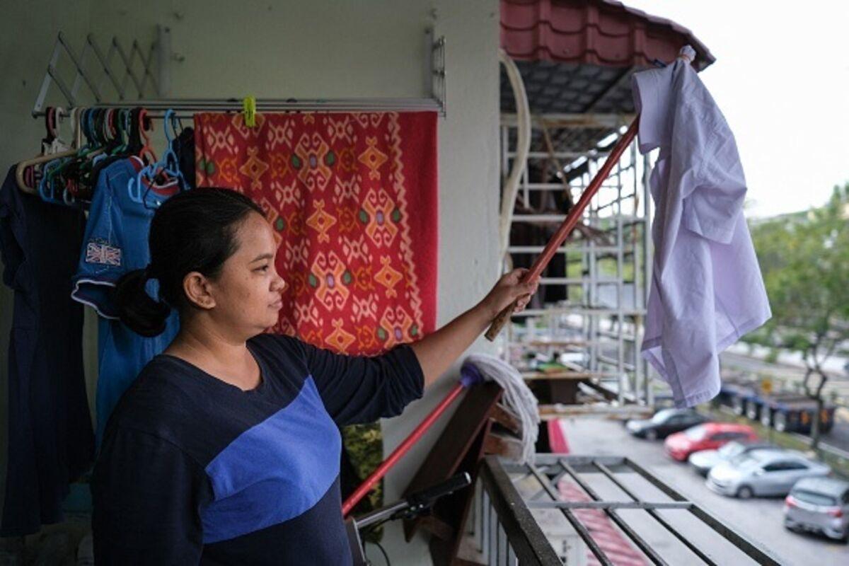 Tilda Kalaivani waves a shirt as a white flag from her apartment balcony in Kuala Lumpur.