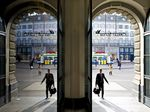 A visitor is reflected in a window as he enters a Credit Suisse Group AG office in Zurich, Switzerland.