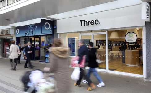 An O2 mobile phone store next to a Three store in Basildon, U.K.