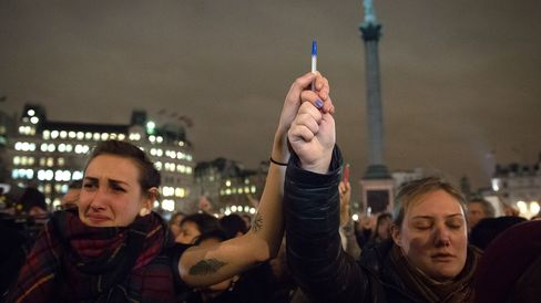 People holds pens and posters in the air as they gather in Trafalgar Square in central London to show their respect for the twelve people killed in Paris today in a terrorist attack at the headquarters of satirical publication 'Charlie Hebdo' on January 7, 2015.
