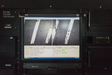 As thousands of still photos are taken by two external cameras of the pavement below, they appear on a screen in the van. Data collected gives specific measurements about the condition of the pavement with visual references recorded by the cameras.