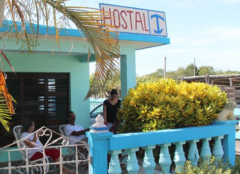 Carlos Jimenez sits on Playa Giron guesthouse's porch with his wife. Photographer: Andrew Willis/Bloomberg
