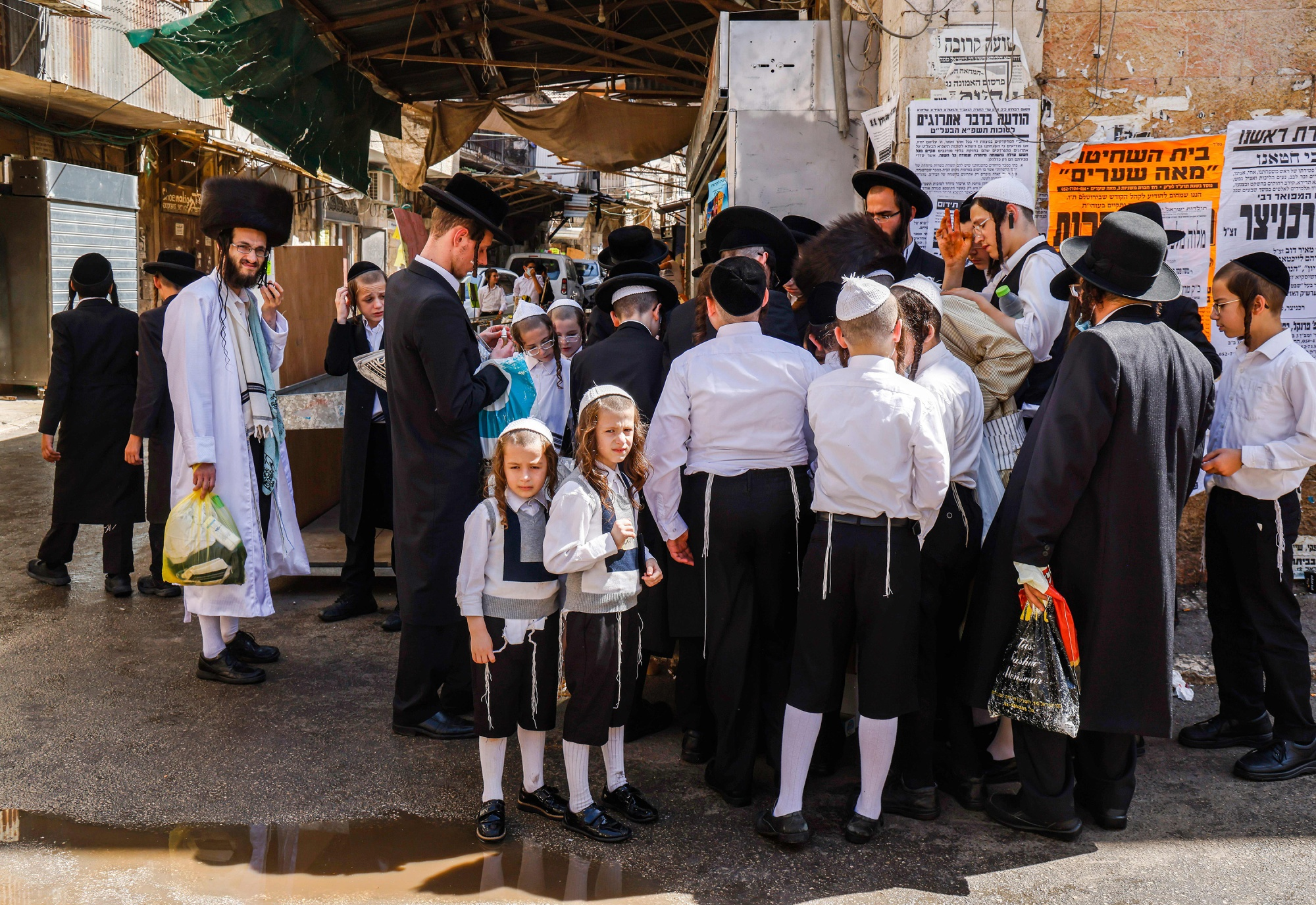 Ultra-Orthodox Jewish men and boys stand along a street corner in the Mea Shearim neighborhood of Jerusalem.