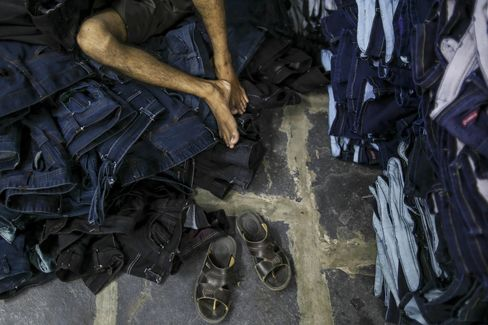 A laborer lies on pile of denim jeans during a break at Aditya jeans washers in Ballari.
