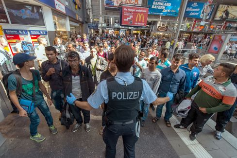 A policeman shows a refugee group the way to the registration office at the central train station in Munich on Aug. 31, 2015. Photographer: Matthias Balk/picture-alliance/dpa/AP Images