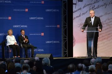 Former Secretary of State Hillary Rodham Clinton and Jeffrey Rosen, president and CEO of the National Constitution Center, listen as former Florida Gov. Jeb Bush speaks before the presentation of the 2013 Liberty Medal in Philadelphia.