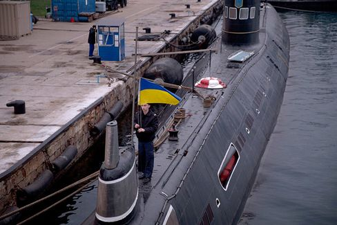 A sailor lowers Ukraine's blue and yellow flag on a submarine at a naval base in Streletskaya Bay in Sevastopol. Ukraine's military command in Kiev is issuing few orders and avoiding displays of force