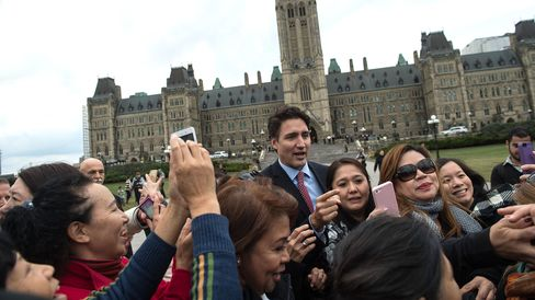 Canadian Liberal Party leader Justin Trudeau poses for photos with tourists as he walks from the parliament to give a press conference in Ottawa on Oct. 20, 2015 after winning the general elections.