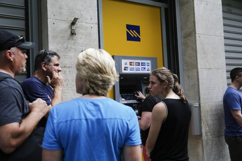 People wait in line at an ATM at a bank in Athens