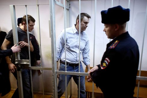 Russian opposition activist and anti-corruption crusader Alexei Navalny, 38, center, and his brother Oleg Navalny, left, enter into the cage at a court in Moscow last year.