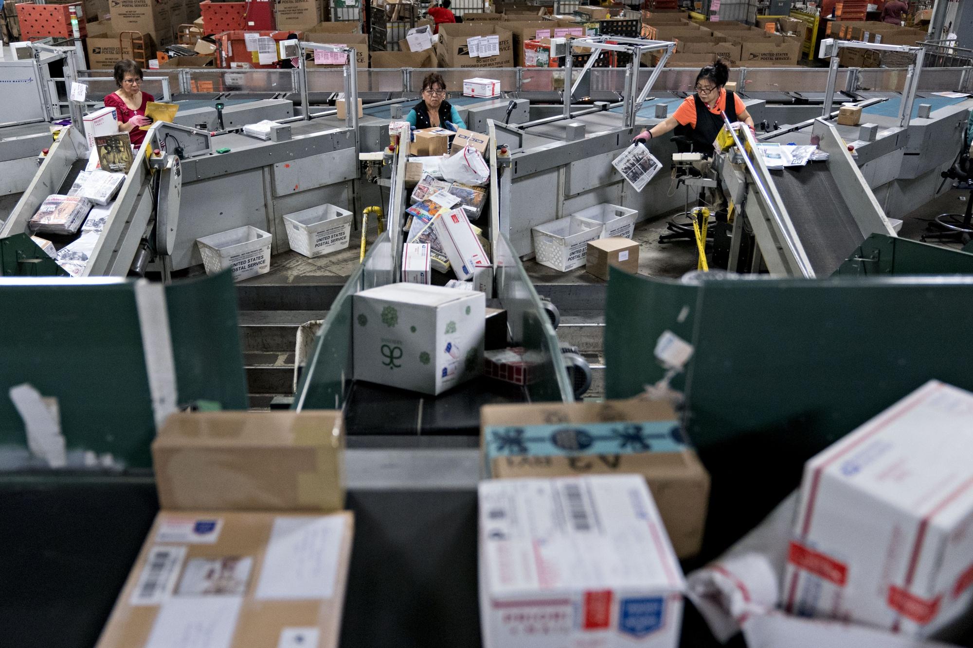Pracownicy sortują paczki w centrum obsługi i dystrybucji USPS (USPS).