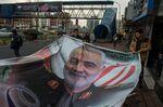 People prepare to hang a poster of Qassem Soleimani, an Iranian commander, following a U.S. airstrike in Iraq, in Tehran, Iran, on Sunday, Jan. 5, 2020.