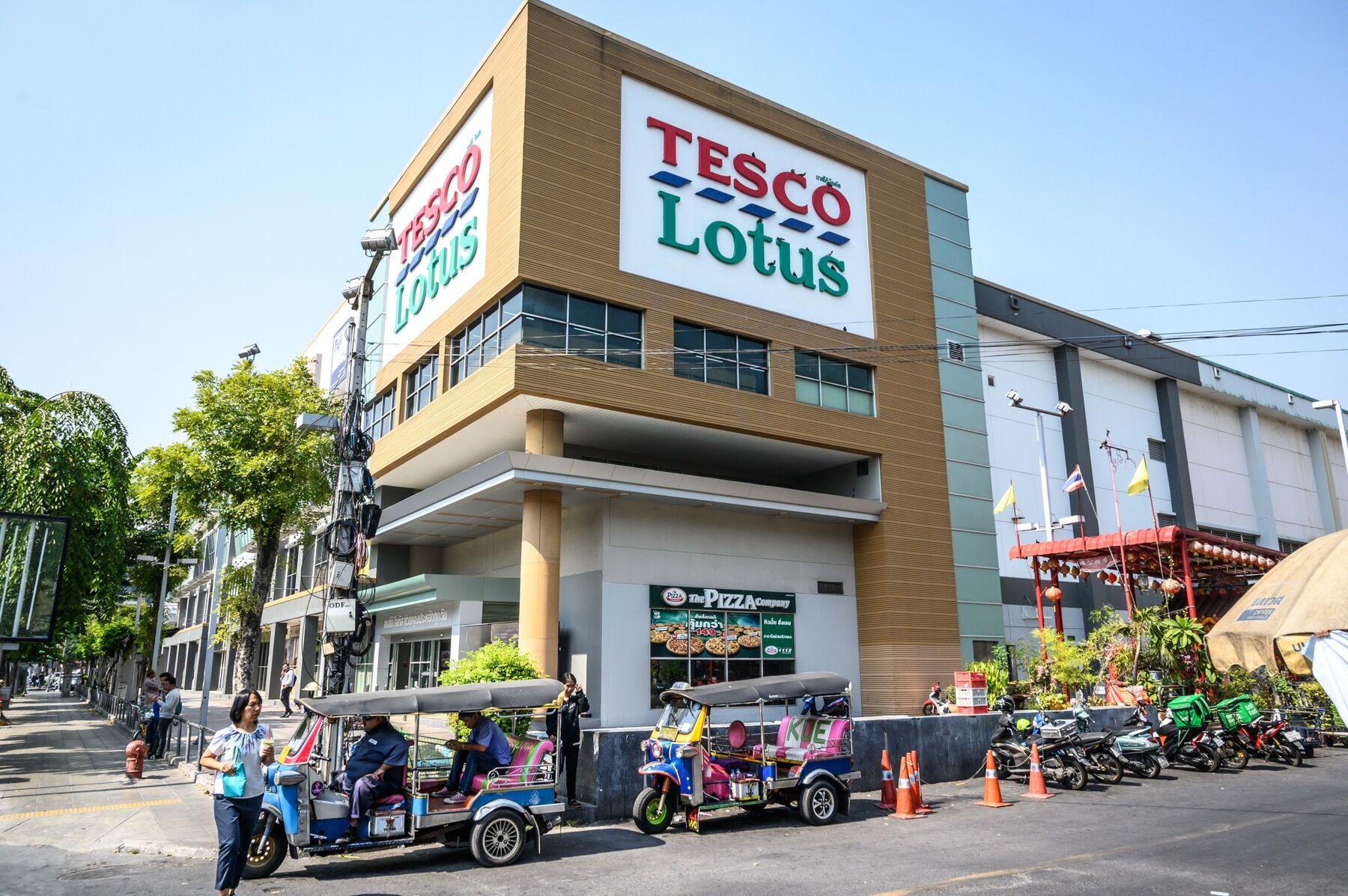 Tuk Tuk drivers wait for customers outside a Tesco-Lotus supermarket in Bangkok