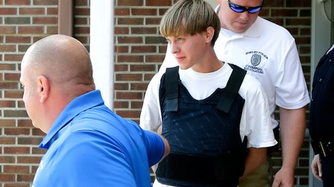 Charleston, S.C., shooting suspect Dylann Storm Roof, center, is escorted from the Shelby Police Department in Shelby, North Carolina, on June 18, 2015.