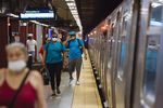 People wearing protective masks walk through the Essex Street subway station in New York, U.S.