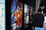 Movie goers line up next to an advertisement for 'Demon Slayer: Kimetsu no Yaiba' outside a movie theater in Tokyo on Oct. 31.