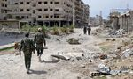 Syrian government soldiers walk past destroyed buildings in the former rebel-held town of Jobar, recently taken by the regime forces, in Eastern Ghouta, on april 1, 2018.