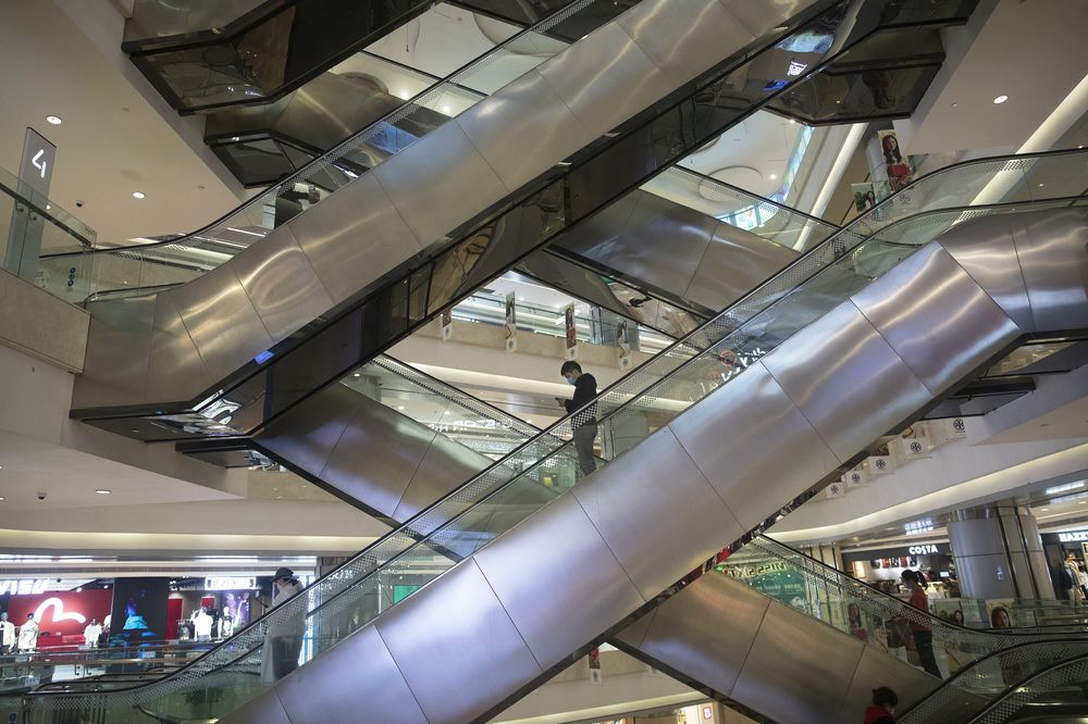 A customer rides an escalator in Wuhan international plaza on March 30.