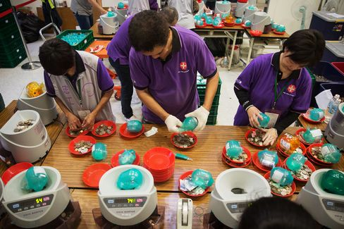 Volunteers unload Taiwanese coins and banknotes from the piggy banks