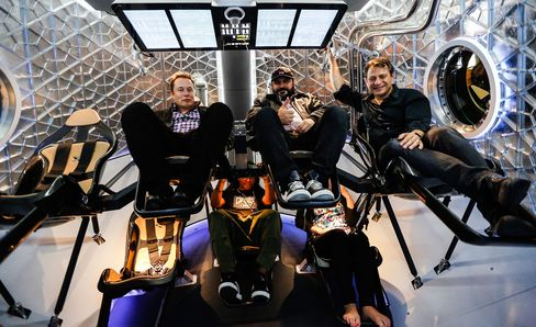 Elon Musk, chief executive officer of Space Exploration Technologies Corp. (SpaceX), left, with guests inside the Manned Dragon V2 Space Taxi in Hawthorne, California, on May 29, 2014. The Dragon V2 manned space taxi, an upgraded version of the unmanned spacecraft Dragon, will be capable of sending a mix of cargo and up to seven crew members to the International Space Station.