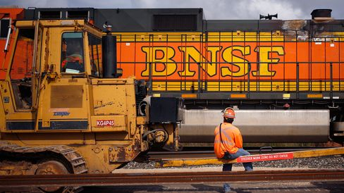 A maintenance-of-way worker watches as an Eastbound intermodal train passes by a track laying machine on Burlington Northern Santa Fe (BNSF) Railway's Southern Transcontinental line in Alva, Oklahoma, U.S. on Wednesday, August 19, 2015. In order to increase capacity and decrease delays, BNSF is working to convert several miles of single track into a double main line. Photographer: Luke Sharrett/Bloomberg