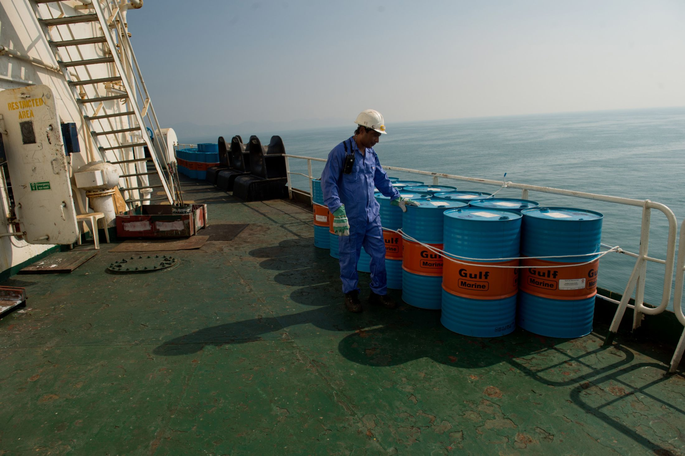 A crew man secures oil drums on the deck near Kharq Island, Iran.