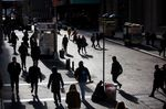 Pedestrians walk along Wall Street near the New York Stock Exchange (NYSE) in New York, U.S.