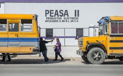 Factory workers at a Regal Beloit Corp. plant, also known as Peasas II, walk to the buses that will take them home after their shift has ended in Acuna, Mexico.