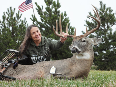 Judi Collora, posing with a buck hunted with her company's doe-in-estrus scent