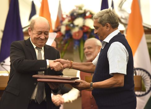 Indian and French defense ministers shake hands after the buying of Rafale fighter jets.