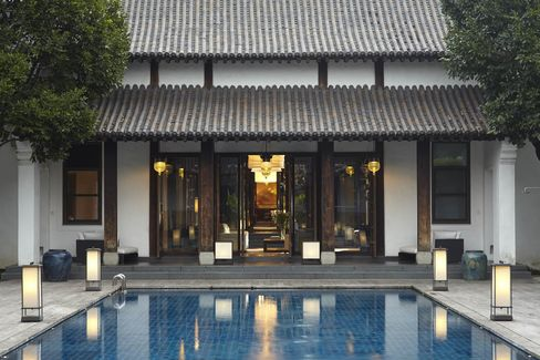 Outside the sitting room, divided by antique Chinese screens, is a softly lit swimming pool.