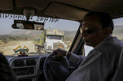 A debris truck drives past a Flying Squad van of the NMMC in Navi Mumbai, India.