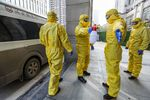 Members of a funeral parlour wearing protective suits disinfecting a colleague after they transferred a body at a hospital in Wuhan in China's central Hubei province, during the virus outbreak in the city on Jan. 30.