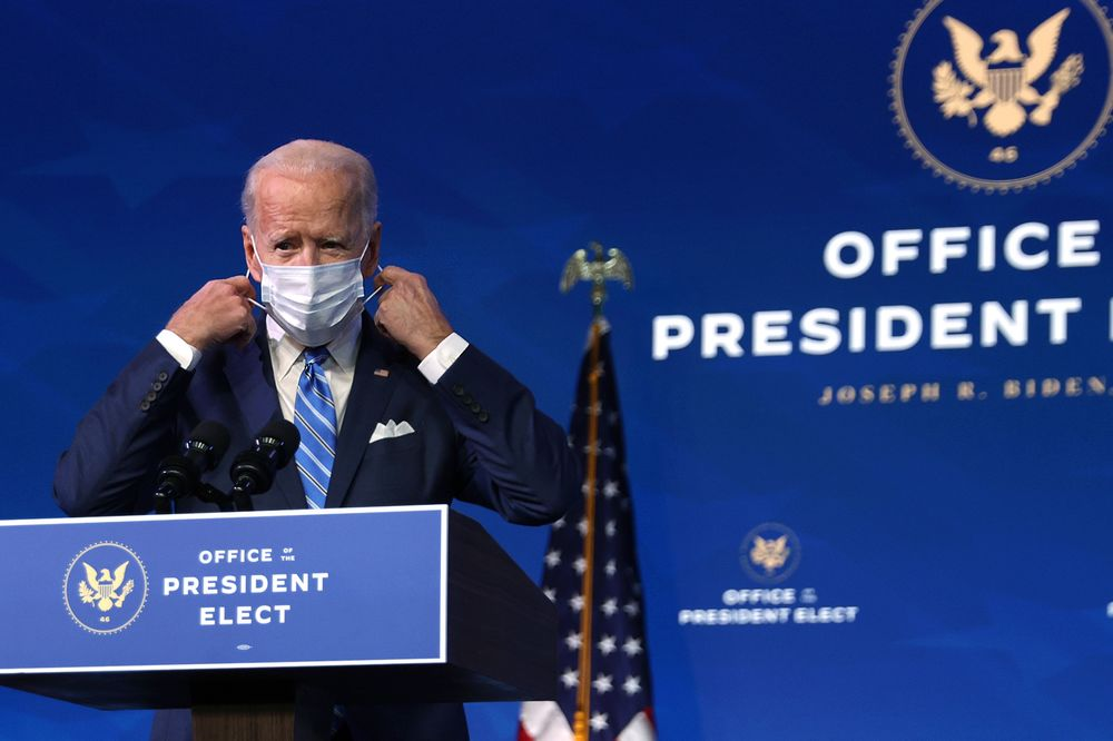 Joe Biden takes off his mask as he arrives at the Queen theaterin Wilmington, Delaware on Jan. 14.