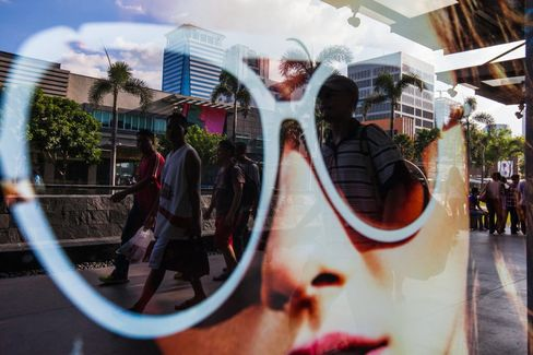 Pedestrians are reflected in a store window display in the Fort Bonifacio district of Manila, the Philippines.