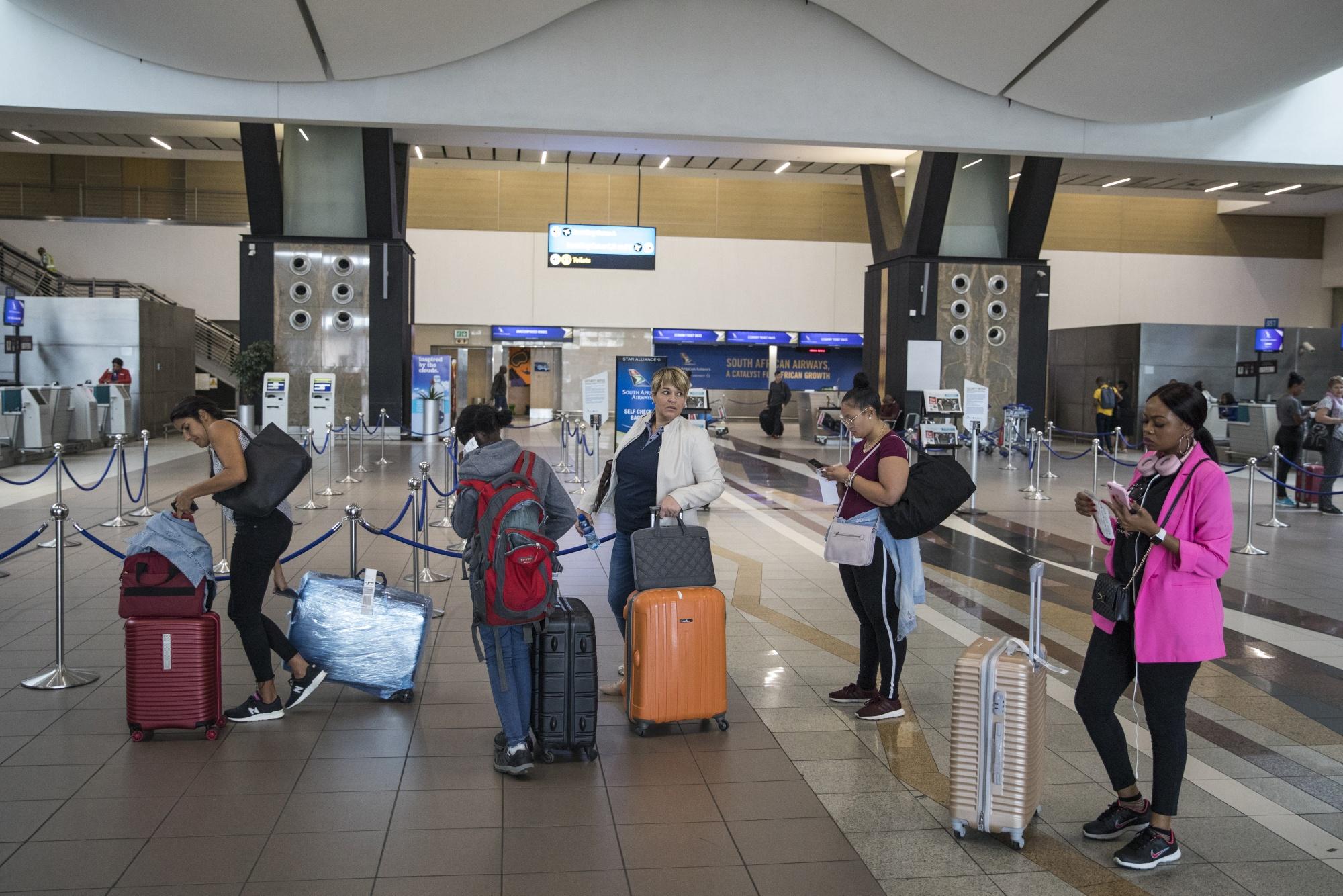 Passengers queueinside Tambo International Airport in Johannesburg.