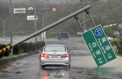 A car drives pass a collapsed traffic sign, toppled by strong winds in Taiwan.