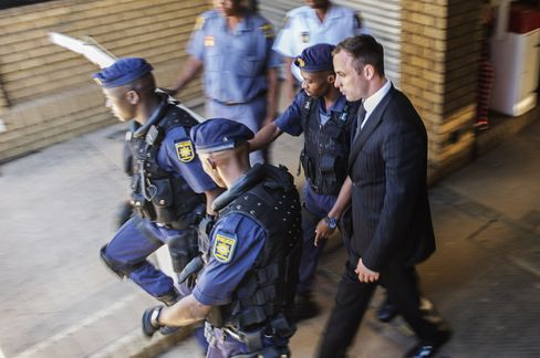 Oscar Pistorius, right, is escorted by policemen at the High Court in Pretoria, on Oct. 21, 2014.
