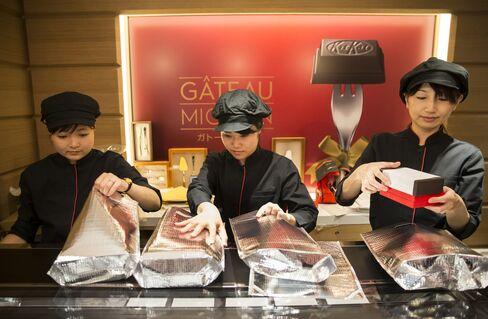 「キットカット ショコラトリー ガトーミニョン」の箱を包装する店員