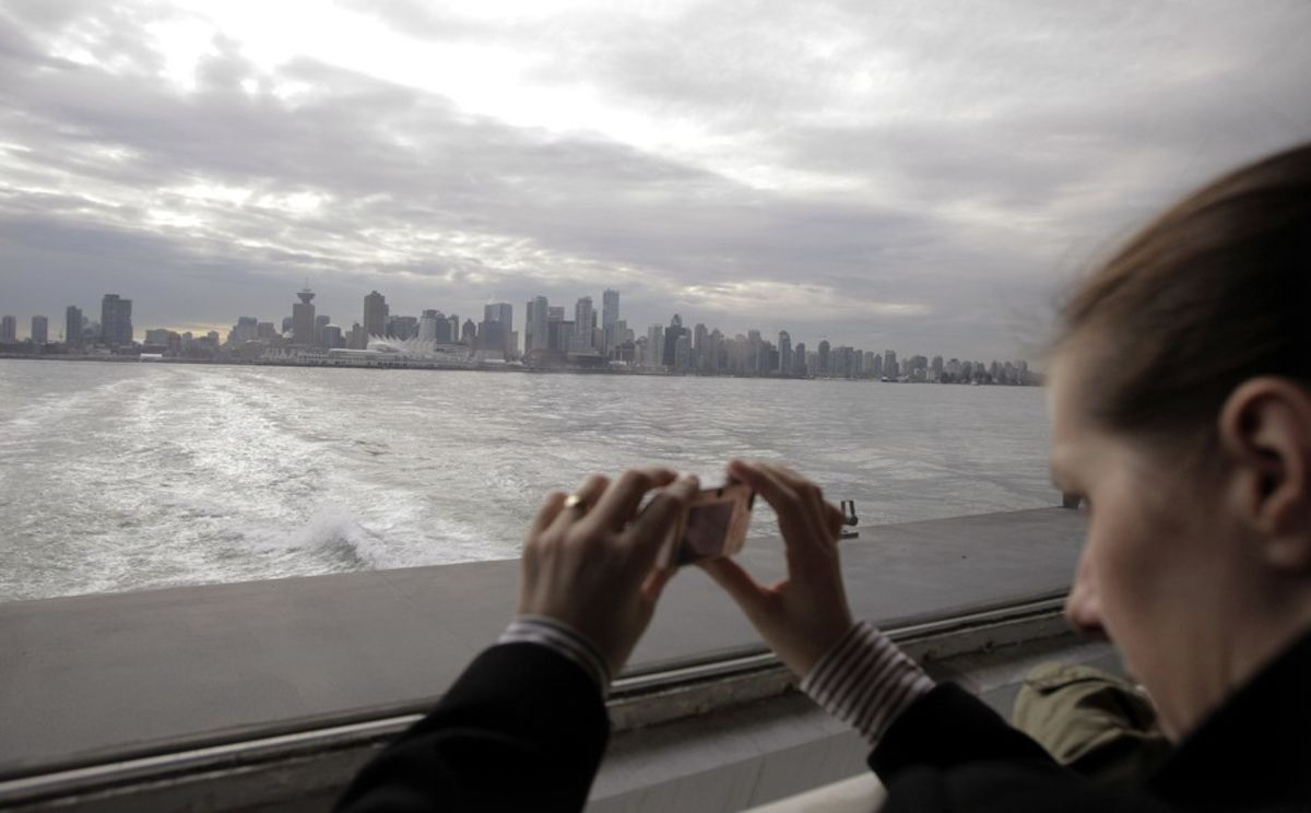 A tourist takes a photo of the Vancouver skyline. The Canadian city expects 10 million visitors this year.