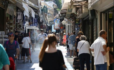 Pedestrians pass gift stores in the Monastiraki district of Athens, Greece, on Thursday, July 2, 2015.