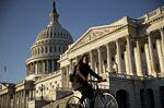 A bicyclist rides past the U.S. Capitol in Washington, D.C., U.S..