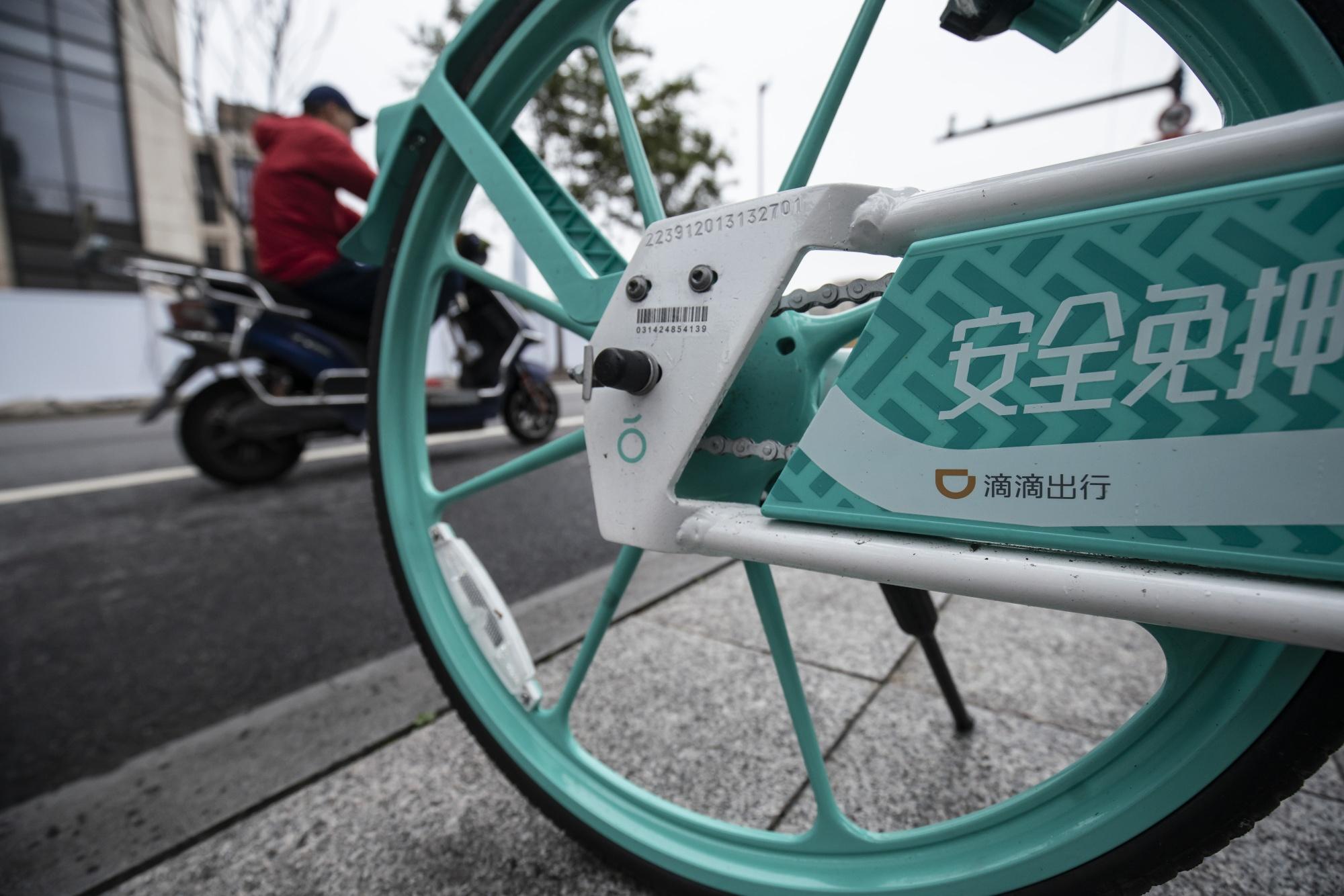 The logo of Didi Chuxing Inc. on a shared-bike standing on the sidewalk in Shanghai.