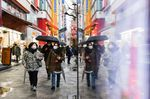 Pedestrians wearing protective masks and holding umbrellas walk in the Akihabara shopping district of Tokyo, Japan.