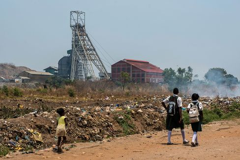 Schoolchildren walk along a dirt road past the South Ore Body Shaft at the Mopani Copper Mines Plc mine in Kitwe.