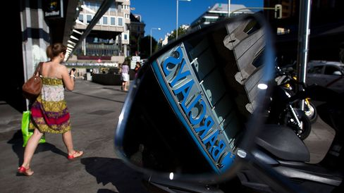 A Barclays logo is seen in the wing mirror of a scooter parked outside a Barclays Plc bank branch in Madrid.