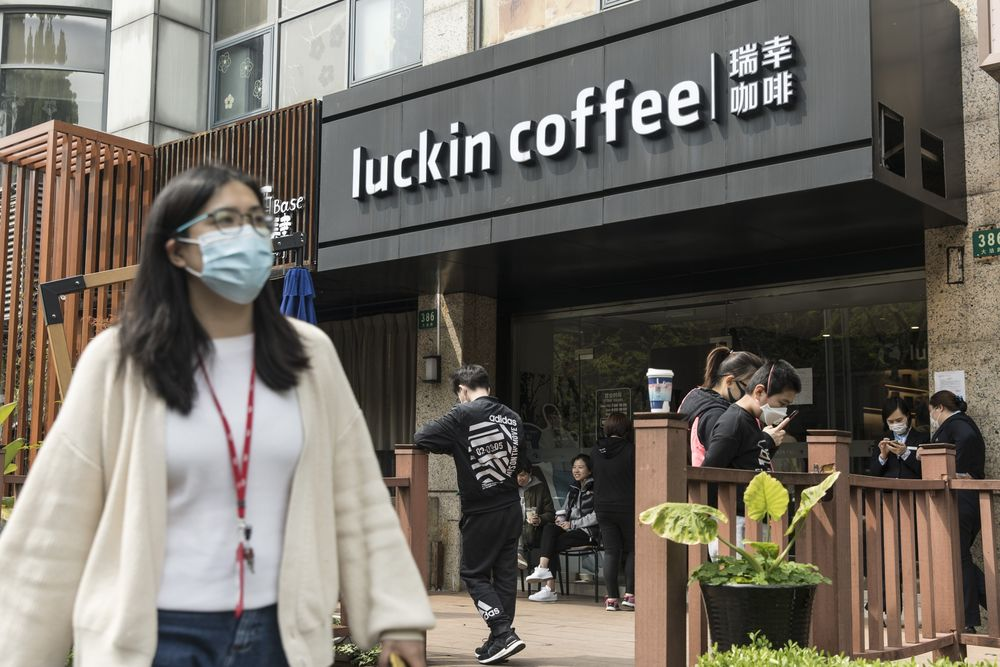 People wearing protective masks gather outside a Luckin Coffee outlet in Shanghai, China on April 3.