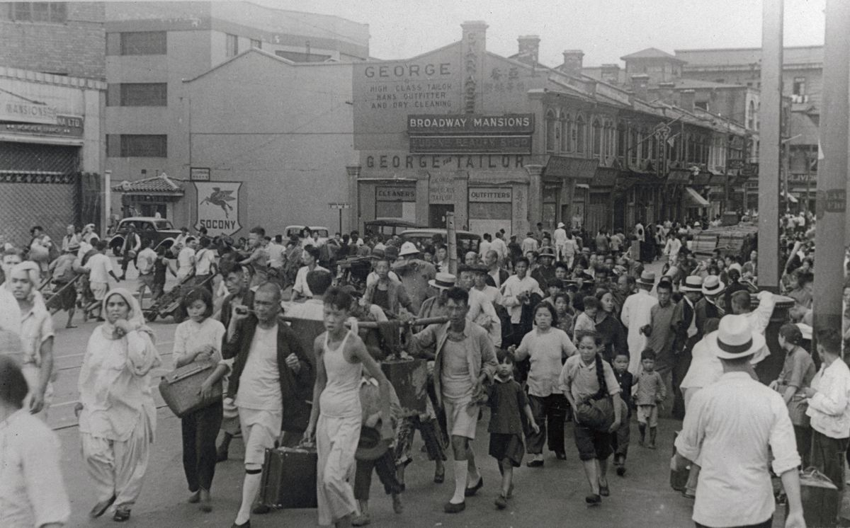 Black and white archival photo of refugees in Shanghai, with men, women and children on foot, carrying luggage
