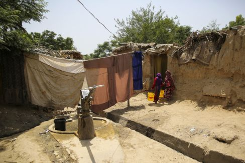 Young Afghan girls carry containers of water from a community hand pump.