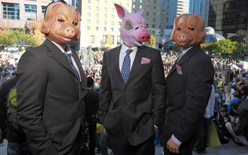 Protesters wear pig masks as people participate in an Occupy protest in Vancouver, on Oct. 15, 2011.